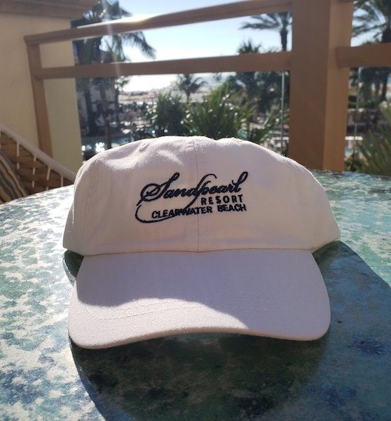 Hat white with embroidered Sandpearl Resort logo in navy