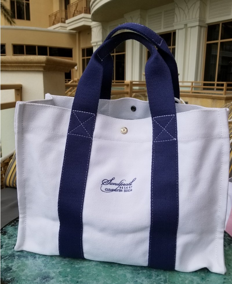 Canvas tote with blue handle and embroidered Sandpearl Resort logo